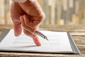 Male hand holding a pen pointing to a line at the end of a contract
